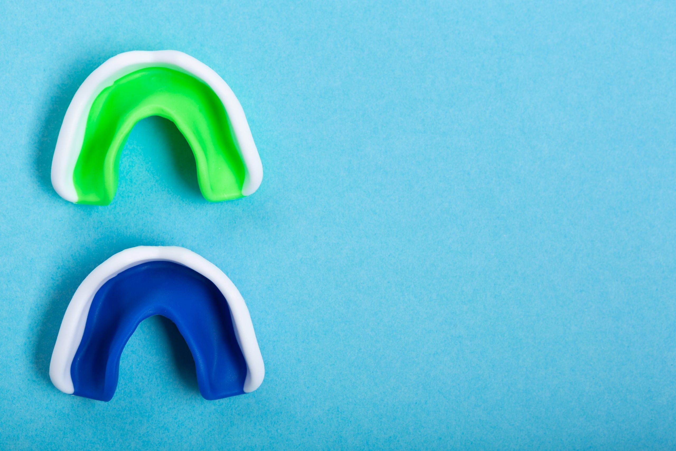 two boxing mouthguards on blue background, sport concept